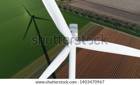 Aerial picture of wind turbine during sundown also showing the long shadow of mast of the energy converter is a device that converts the winds kinetic power into electrical electricity #1403470967