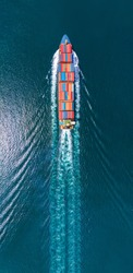 Aerial portrait view of smart cargo ship with contrail in the ocean sea ship carrying container from custom container depot go to ocean concept freight shipping by ship service.