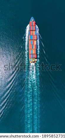 Aerial portrait view of smart cargo ship with contrail in the ocean sea ship carrying container from custom container depot go to ocean concept freight shipping by ship service. Сток-фото ©