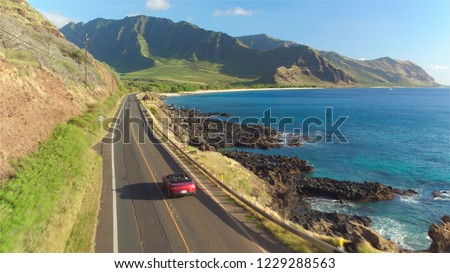 AERIAL: Red convertible car driving along the picturesque coastal road above dramatic rocky shore towards beautiful volcanic mountains. Happy young couple on summer vacation traveling at the seaside