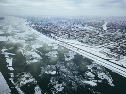 aerial river with ice near the city on a winter day