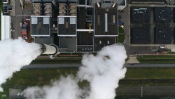 Aerial satellite view of coal fired power station is a thermal plant which burns a fossil fuel to produce electricity by converting heat of combustion into mechanical energy