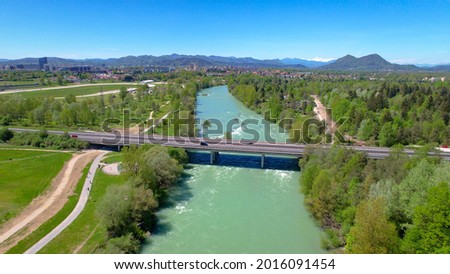 AERIAL: Scenic drone point of view of a highway crossing the emerald river crossing the lush green Slovenian landscape. Sava river coursing through the vibrant Ljubljana suburbs on sunny summer day. Stok fotoğraf ©