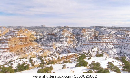 AERIAL: Scenic drone shot of a breathtaking canyon in Utah in the wintertime. Flying over the red cliffs and valleys lightly covered in the first snow of the winter. Picturesque canyons in the USA. #1559026082
