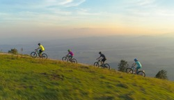 AERIAL: Scenic shot of a group of friends riding their mountain bikes uphill on a sunny morning. Active tourists pedalling mountain bicycles up a narrow dirt track in the beautiful green mountains.