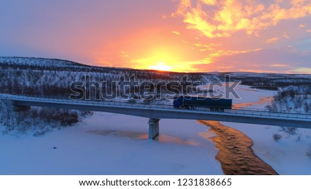 AERIAL: Semi truck crossing the bridge above icy river in the winter at sunset #1231838665