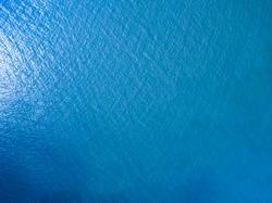 Aerial shoot top down of a smooth blue ocean.