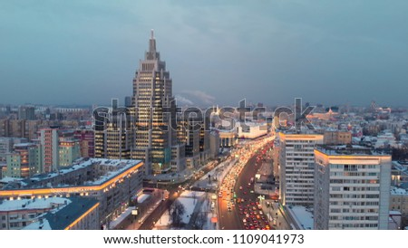 """Aerial shooting of Moscow Garden Ring in the evening with camera going up. City lights in the dusk. Business center """"Oruzheiny"""" tower at sunset. #1109041973"""