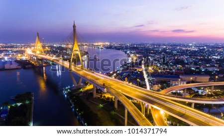 Aerial Shot : beautiful night scene of Bhumibol Bridge, also known as the Industrial Ring Road Bridge, The bridge crosses the Chao Phraya River in Bangkok, Thailand, for transportation concept #1014371794