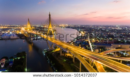Aerial Shot : beautiful night scene of Bhumibol Bridge, also known as the Industrial Ring Road Bridge, The bridge crosses the Chao Phraya River in Bangkok, Thailand, for transportation concept #1014372037