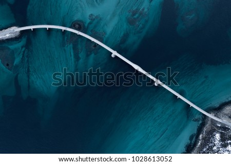Aerial shot of a bridge over sea strait. Visible depth with blue and green colours near Tromso. Sommaroy, Norway #1028613052