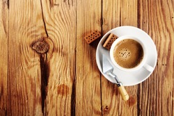 Aerial Shot of a Conceptual Cup of Espresso on a Plate Served on the Wooden Table with Trowel and Small Bricks on the Side