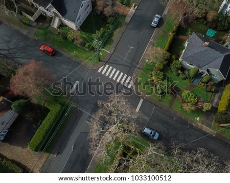Aerial shot of a four way intersection in a small village  #1033100512