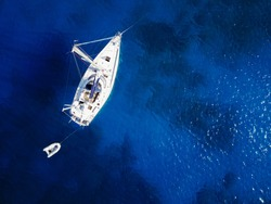 Aerial shot of beautiful blue lagoon at hot summer day. Top view of sailing boat ready for cruise.