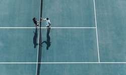 Aerial shot of professional tennis players handshakes at the net. Sportsmen shaking hands over the net on hard court.