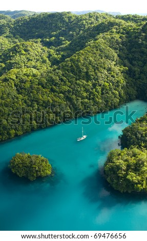 Aerial shot of sheltered bay with private sail boat