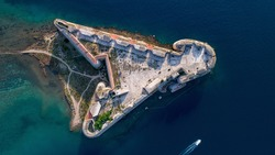 Aerial shot of St. Nicholas Fortress and a boat passing by