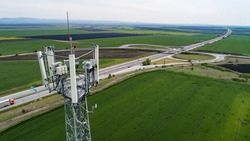 Aerial shot of telecommunication tower with highway on the back. Telecom tower antennas and satellite transmits the signals of cellular 5g 4g 3g lte mobile signals to the consumers and smartphones.