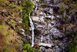 aerial shot of the waterfall of davies creek falling over the rocks