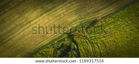 Aerial shot of tractor on the agricultural field sowing. Red tractors working on the agricultural field with sprayer.