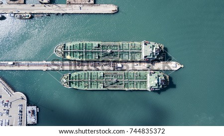 Aerial shot of two tanker ships anchored at the oil terminal at port - top down