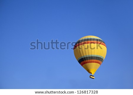 Aerial shot of yellow hot air balloon with colored bands in a clear blue sky. Generic image, shot location, Cappadocia, Anatolia, Turkey