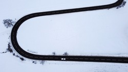 Aerial shot with drone of road curve with moving car in winter