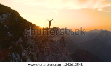 AERIAL, SILHOUETTE, SUN FLARE: Flying behind unrecognizable athletic man celebrating a successful ascent onto a scenic cliff in Julian Alps. Hiker outstretches arms as he observes the golden sunset #1343613548