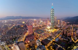 Aerial skyline of Downtown Taipei at dusk, the capital city of Taiwan, with 101 Tower standing next to World Trade Center in Xinyi Financial District and oval shaped Taipei Dome located in nearby area