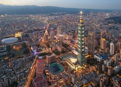 Aerial skyline of Downtown Taipei at dusk, vibrant capital city of Taiwan, with 101 Tower standing out amid skyscrapers in Xinyi Commercial District and oval shaped Taipei Dome located in nearby area