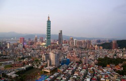 Aerial skyline of Downtown Taipei at dusk, vibrant capital city of Taiwan, with 101 Tower standing out among skyscrapers in Xinyi Commercial District and oval shaped Taipei Dome located in nearby area