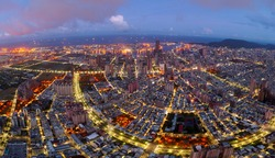 Aerial skyline of Kaohsiung at dusk, a vibrant seaport city in South Taiwan, with the landmark 85 Sky Tower standing by the harbor and the lights of crisscrossing streets dazzling in blue twilight