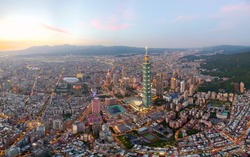 Aerial skyline of Taipei, vibrant capital city of Taiwan, with 101 Tower standing out in Xinyi Commercial District, the oval roof of nearby Taipei Dome & distant mountains on horizon under sunset sky