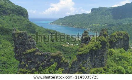 Stock Photo AERIAL: Small coastal village is hidden in vibrant green valley under breathtaking mountains overgrown by dense exotic forest. Flying over the green jungle surrounding village by the deep blue ocean.