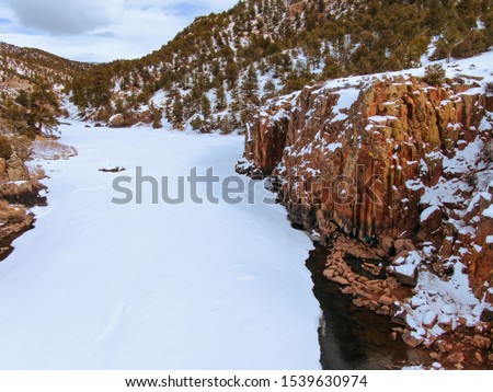 AERIAL: Spectacular winter landscape surrounds the young tourist couple relaxing in hot springs of Colorado. Unrecognizable man and woman sit and relax in the therapeutic water of Radium hot springs. stock photo