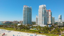 Aerial stock Miami Beach Spring break vacation. Beautiful sunny day at South Beach, Florida. Aerial over hotels, condos and beach goers on South Beach. Aerial video stock footage, Miami, Florida.