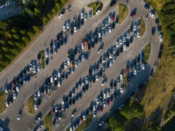 Aerial straight down view of busy full parking lot in summer time next to marina at lake Ontario. Many cars parked with boat trailers.