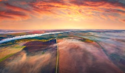 Aerial summer view from flying drone of plowed field. Amazing sunrise of Ukrainian countryside, Foggy landscape of cultivated fields with old country road, Ternopil, Ukraine, Europe.