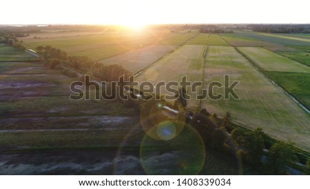 Aerial sundown photo of rural area or countryside is a geographic zone that is located outside towns and cities showing both naturals as agricultural areas and sunflare rings over lens #1408339034