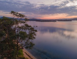 Aerial sunrise waterscape over the bay with clouds and reflections at Woy Woy on the Central Coast, NSW, Australia.