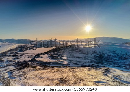 AERIAL: Sunset golden light over Norwegian snowy winter mountains with birch and pine trees, early spring, calm blue skies. Atoklinten mountain area, Joesjo, Lappland municipality, Northern Sweden Stock foto ©