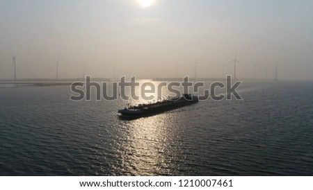 Aerial sunset photo of barge a flat-bottomed ship built mainly for river and canal transport of material goods and very heavy or bulky also showing wind turbines in background
