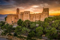 Aerial sunset view of Cullera castle and Sanctuary of the Virgen del Castillo above the popular summer resort vacation beach town near Valencia Spain
