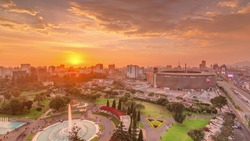Aerial sunset view of the National stadium in the Peruvian capital Lima with Via Expresa highway timelapse. Landscape of Park of the Reserve and city skyline on a background in South America. Peru