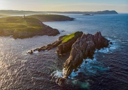 Aerial sunset view off the coast of the Avalon Penninsula near Ferryland, Newfoundland. The Ferryland Head lighthouse can be seen on the mainland.