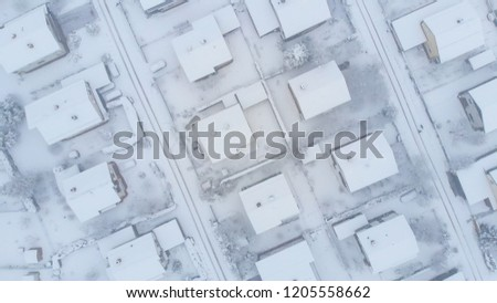 AERIAL, TOP DOWN: Blizzard covers roofs and asphalt roads leading through the tranquil suburbs. Flying above the trails in the snow covered streets and private properties in the idyllic village.