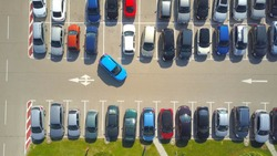AERIAL TOP DOWN: Flying above female bad driver incapable to park a car on parking space in crowded parking lot. Woman having problems, unable to park a car in parking spot. Parking fail on parkspace