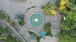 Aerial top down 4k view of square with fountains and people walking in the Park.