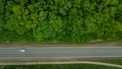 Aerial top down 4k view of white car driving on rural road in forest. Cinematic drone shot flying over gravel road in pine tree forest