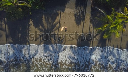 AERIAL, TOP DOWN: Lonely topless surfer sitting on sandy beach, looking into the horizon. Unrecognizable man sitting next to wooden surfboard on remote sandy beach on cool tropical island in Indonesia #796818772